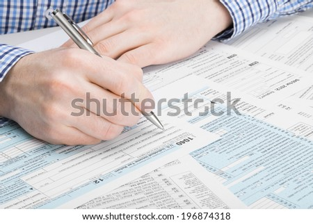 Tax Form 1040 - man performing tax calculations - stock photo