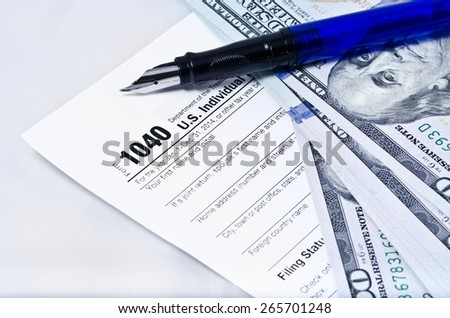 Tax form 1040 on a gray background, blue pen, and 100 dollar bills - stock photo