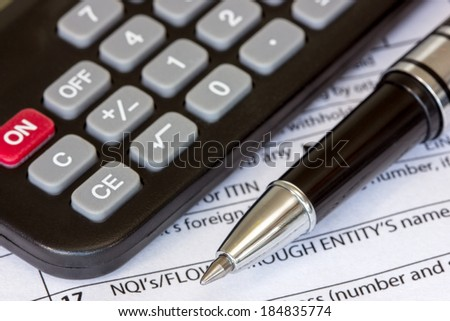 Tax form 1042-S with pen and calculator - stock photo