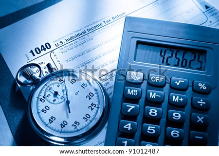 Tax form, stopwatch and calculator