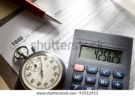 Tax form, stopwatch, calculator and pen - stock photo