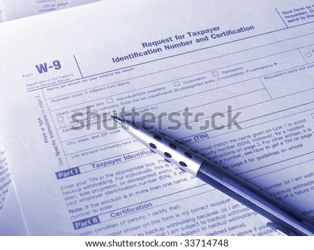 Tax form W-9 and pen. Toned blue. Shallow DOF. - stock photo
