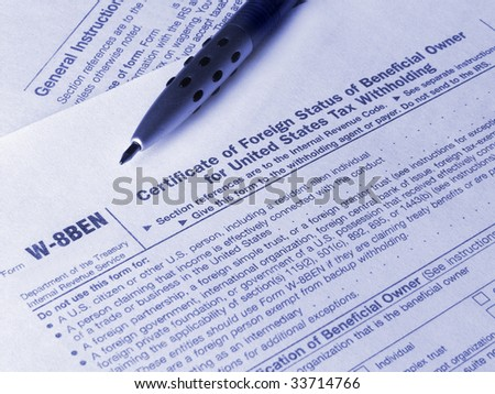 Tax form W-8BEN and pen. Toned blue. Shallow DOF. - stock photo