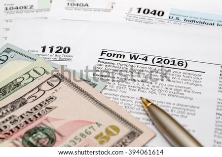 tax form w4, 1040, 1120 with pen and us dollar - stock photo