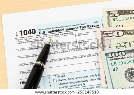 Tax form with banknote, and pen