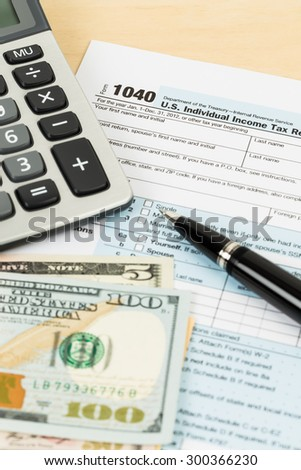 Tax form with banknote, calculator, and pen - stock photo