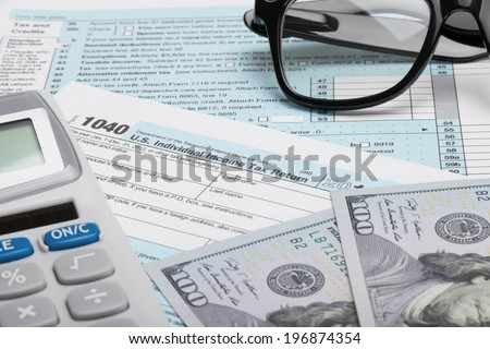 Tax Form 1040 with calculator, dollars and glasses - stock photo