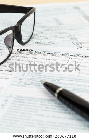 Tax form with glasses, and pen - stock photo