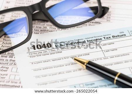 Tax form with glasses, and pen taxation concept