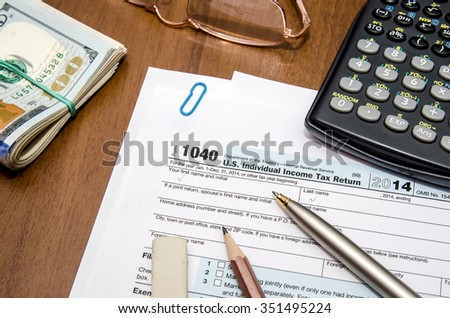 tax form 1040 with glasses, pen and dollar