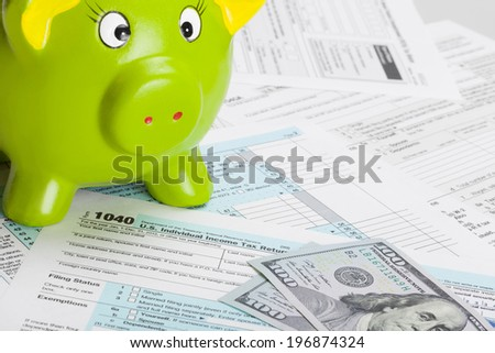 Tax Form 1040 with green piggy bank - stock photo
