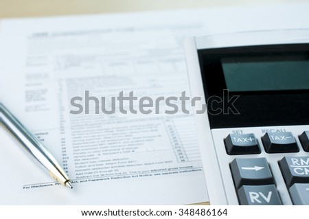 Tax form with pen and calculator - stock photo