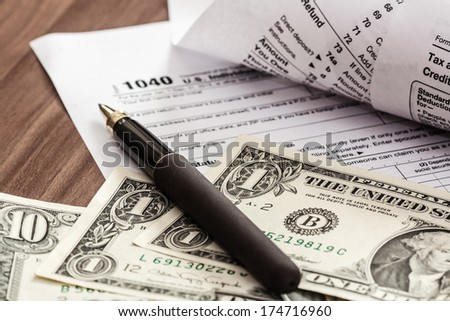 tax form with pen and dollars on wood desk; U.S. individual income tax return form 1040