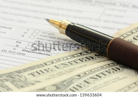 tax form with pen and dollars; U.S. individual income tax return form 1040 - stock photo