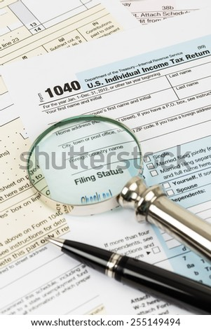 Tax form with pen and magnifying glass taxation concept - stock photo