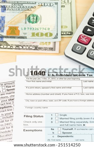 Tax form with pen, banknote, and calculator taxation concept - stock photo