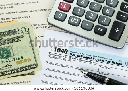 Tax form with pen, calculator, and dollar banknote taxation concept