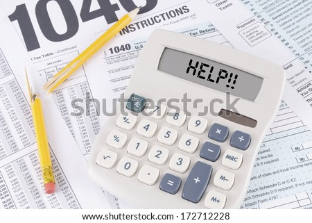 Tax Forms and Broken Pencil with a Calculator that has HELP!! spelled out on the display - stock photo