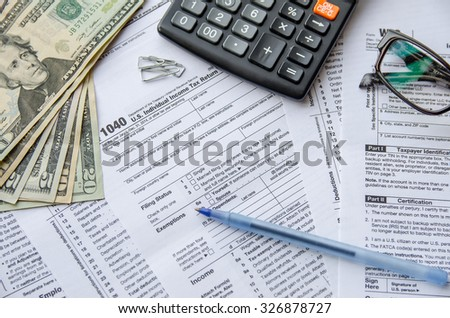 tax forms 1040 with the glasses, money and the pen