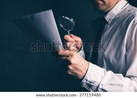 Tax inspector doing financial auditing, businessman reading business report or contract footnotes disclaimer with magnifying glass, retro toned, selective focus - stock photo