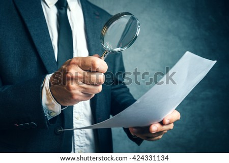 Tax inspector investigating financial documents through magnifying glass, forensic accounting or financial forensics, inspecting offshore company financial papers, documents and reports. - stock photo