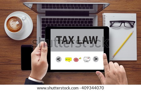 Tax Law Business Concept, on the tablet pc screen held by businessman hands - online, top view - stock photo