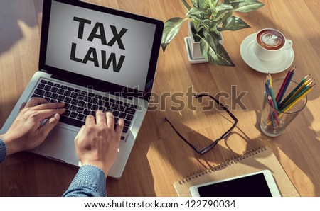 TAX LAW                man hand on table Business, coffee, Split tone - stock photo