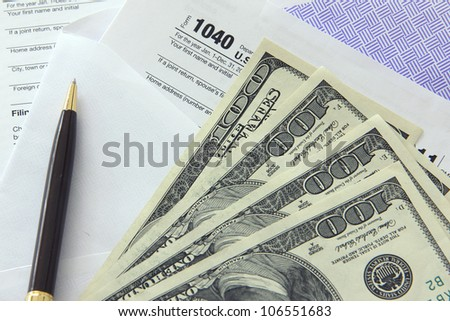 Tax papers in an envelope with 100 dollar bills