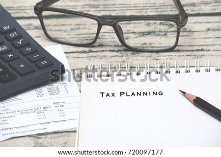 Tax planning concept. Calculator, receipt, eyeglasses and notepad.