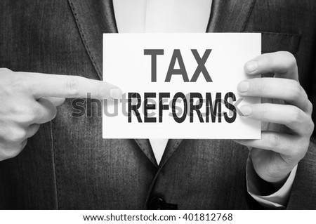 Tax Reforms. Man holding a card with a message text written on it.