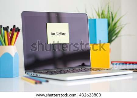 Tax Refund sticky note pasted on the laptop - stock photo