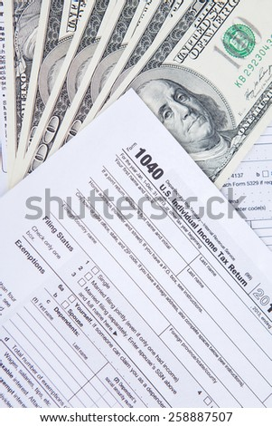 Tax return concept with dollar money on the tax form, shot in the studio