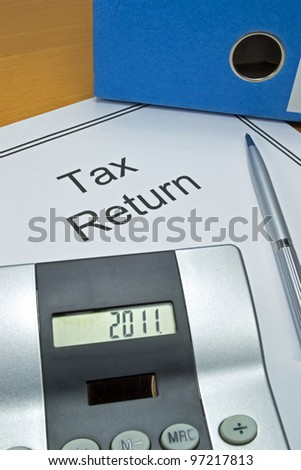 Tax return papers for 2011 next to folder and calculator
