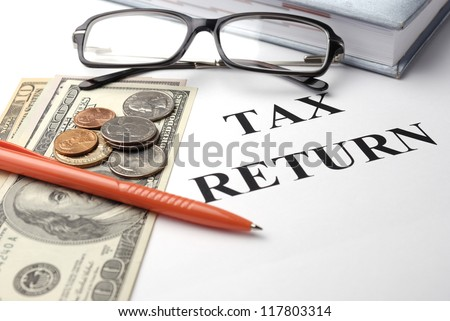 Tax return papers with glasses, pen and money - stock photo