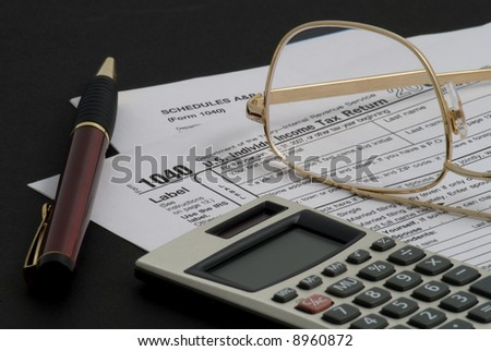 Tax returns, calculator, pen and glasses