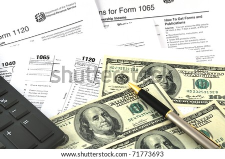 Tax Season. The concept image with a calculator, money and tax return forms.