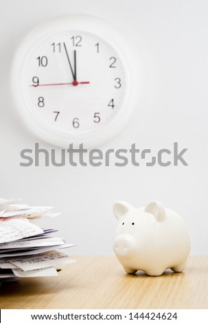 Tax time. A stack of bills next to a piggy bank with a clock behind - stock photo