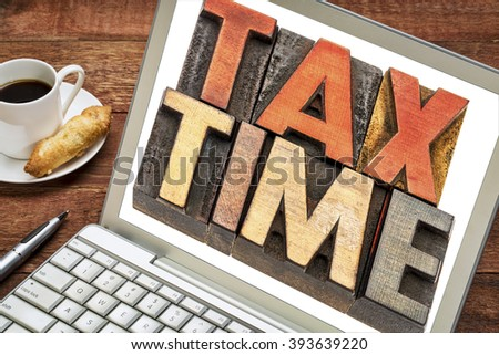 tax time word abstract -  text in vintage letterpress wood type printing block on a laptop screen with a cup of coffee - stock photo
