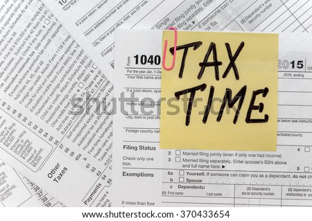 Tax Time written on yellow sticker note with paperclip to tax form - stock photo