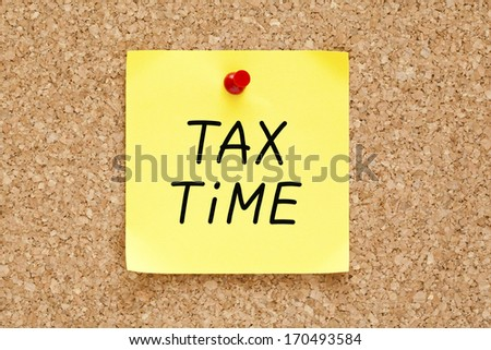 Tax Time written on yellow sticky note pinned with red push pin on cork board. - stock photo