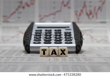 Tax word with calculator on newspaper background