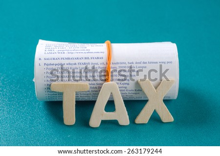 Tax word with rolled receipts - stock photo