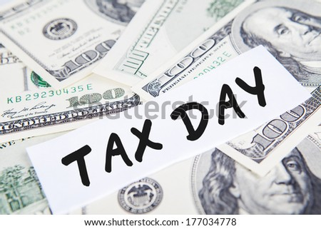 Taxes concept with money and text of tax day - stock photo