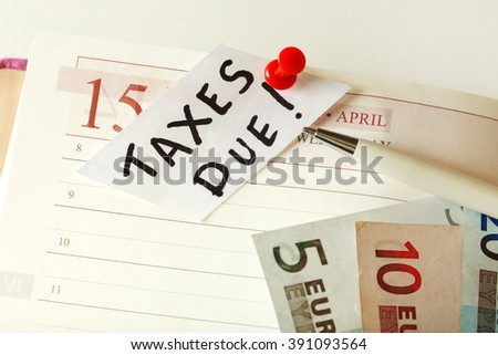 Taxes due  pinned in the planner with euro bills, close up - stock photo