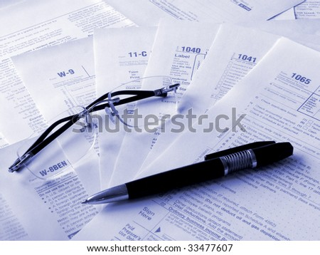 Taxes forms, pen and glasses. Toned blue. Shallow DOF. - stock photo