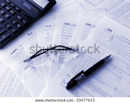 Taxes forms, pen, glasses and calculator. Toned blue. Shallow DOF. - stock photo