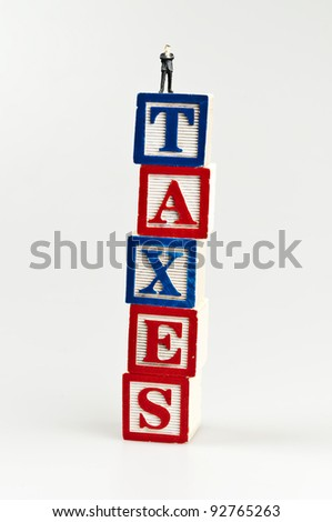 Taxes word and toy business man - stock photo