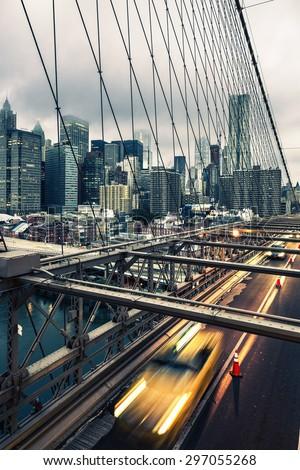 Taxi cab crossing the Brooklyn Bridge in New York, Manhattan skyline in background - stock photo