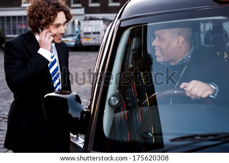 Taxi cab driver communicating with male passenger - stock photo