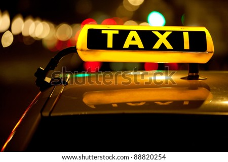 Taxi cab sign on top of the vehicle at nighttime - stock photo